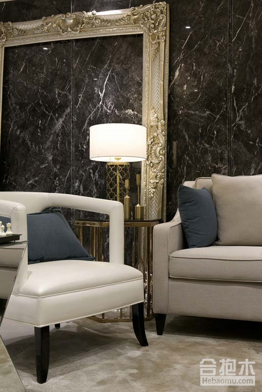 左侧转入客厅,一个雕刻华丽的金色巴洛克风格画框斜靠在一堵造型现代的黑色大理石墙面上,细致的雕花与电视墙和天棚的雕花线条相互辉映,现代格调与欧式元素的融合、尺度、色彩在这个空间完美交汇,呈现出高贵、雅致又不失格调的独特品味。